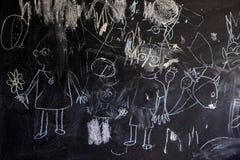 Enfants dessinant avec la craie sur une famille heureuse de tableau noir d'école Photographie stock