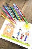 Enfants dessinant la famille heureuse près de leur maison Image libre de droits