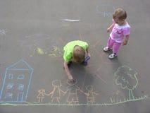 Enfants dessinant sur l'asphalte photos libres de droits