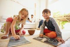 Enfants dessinant tandis que leur père à l'arrière-plan Photographie stock