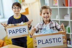 Enfants diligents heureux montrant la consommation consciente tout en tenant des boîtes images stock