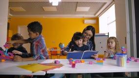 Enfants divers avec le professeur apprenant dans la salle de classe banque de vidéos