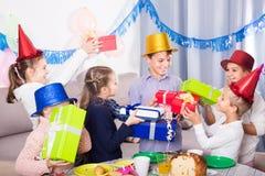 Enfants donnant des présents au petit garçon pendant la partie Photo stock