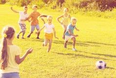 Enfants donnant un coup de pied le football en parc Images libres de droits