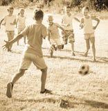 Enfants donnant un coup de pied le football en parc Image libre de droits