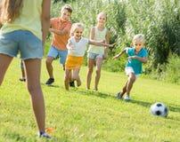 Enfants donnant un coup de pied le football en parc Image stock