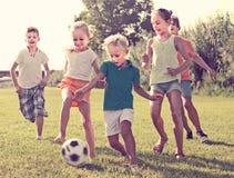 Enfants donnant un coup de pied le football en parc Photos libres de droits