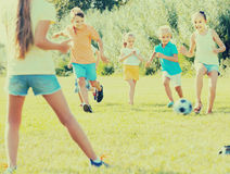 Enfants donnant un coup de pied le football en parc Photos stock