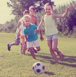 Enfants donnant un coup de pied le football en parc Images stock