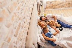 Enfants dormant avec le chat et les parents Image libre de droits