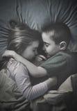 Enfants dormant ensemble la nuit dans le lit Images libres de droits