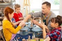 Enfants dou?s ?coutant le professeur et sculptant des mod?les d'argile images libres de droits