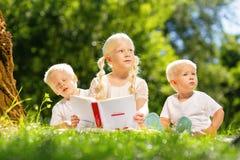 Enfants doux lisant un livre intéressant en parc photo libre de droits