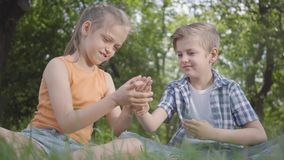 Enfants drôles du portrait deux se reposant sur l'herbe dans le jeu de parc Le garçon jouant avec un insecte, fille essayant de l clips vidéos