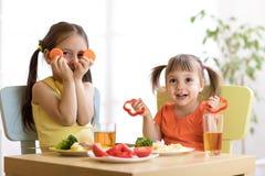 Enfants drôles jouant et mangeant dans le jardin d'enfants Photos stock