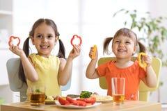 Enfants drôles jouant et mangeant dans le jardin d'enfants Image stock