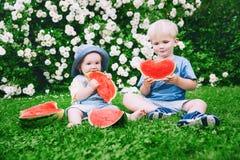 Enfants drôles mangeant la pastèque sur la nature à l'été Image libre de droits