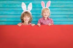 Enfants drôles portant le lapin de Pâques images libres de droits