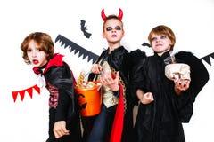 Enfants drôles riants dans des costumes dans Halloween Tour ou festin Images libres de droits