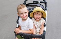 Enfants drôles s'asseyant dans la poussette dehors photographie stock libre de droits