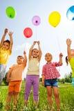 Enfants drôles avec des ballons dans le ciel Photo libre de droits