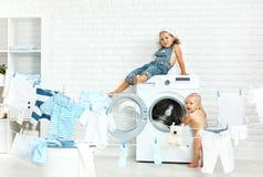 Enfants drôles de petites aides soeur et frère heureux dans la blanchisserie à Images libres de droits