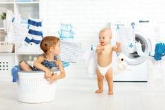 Enfants drôles de petites aides soeur et frère heureux dans la blanchisserie à Photo libre de droits
