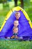 Enfants drôles et chien regardant de la tente Image stock
