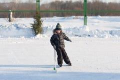 Enfants drôles heureux jouant l'hockey à la piste Photo stock