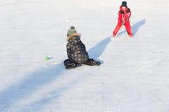 Enfants drôles heureux jouant l'hockey à la piste Photo libre de droits