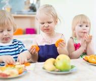 Enfants drôles mangeant des fruits dans le jardin d'enfants Images libres de droits