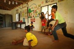 Enfants déshérités par aide avec l'éducation Images stock