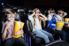 Enfants effrayés observant le film 3D dans le cinéma Photographie stock libre de droits