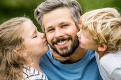 Enfants embrassant le père avec amour Images libres de droits