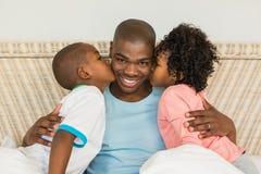 Enfants embrassant le père dans le lit Photographie stock libre de droits