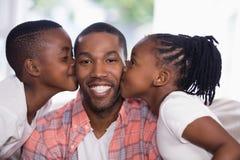 Enfants embrassant le père de sourire à la maison Photos stock