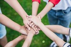 Enfants empilant des mains tout en se tenant sur l'herbe verte Images stock