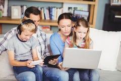 Enfants employant des technologies avec des parents sur le sofa Photos stock