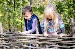 Enfants en Autumn Outfit Playing à la barrière en bois Photo stock