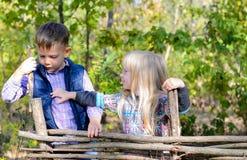 Enfants en Autumn Outfit Playing à la barrière en bois Images stock