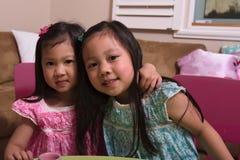 Enfants en bas âge asiatiques étreignant et souriant à l'appareil-photo Image libre de droits