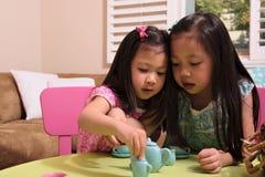 Enfants en bas âge asiatiques jouant avec le service à thé Photo libre de droits