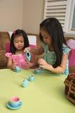 Enfants en bas âge asiatiques jouant avec le service à thé Photographie stock