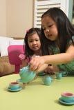 Enfants en bas âge asiatiques jouant avec le service à thé de jouet image libre de droits