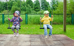 Enfants en bas âge balançant sur une oscillation Photographie stock