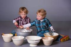 Enfants en bas âge blonds jouant avec des batteries de cuisine Photos stock