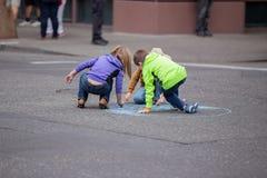Enfants en bas âge dessinant sur une rue photographie stock libre de droits
