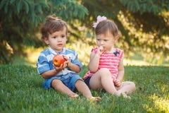 Enfants en bas âge drôles d'enfants s'asseyant ensemble partageant la nourriture de pomme photographie stock libre de droits