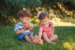 Enfants en bas âge drôles d'enfants s'asseyant ensemble partageant la nourriture de pomme image stock