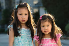 Enfants en bas âge féminins asiatiques souriant à l'appareil-photo au coucher du soleil Image stock